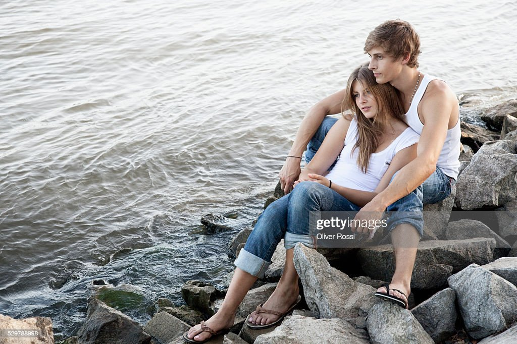 Young couple sitting on rocks by the water : ストックフォト