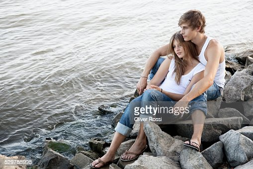 Young couple sitting on rocks by the water : Foto stock