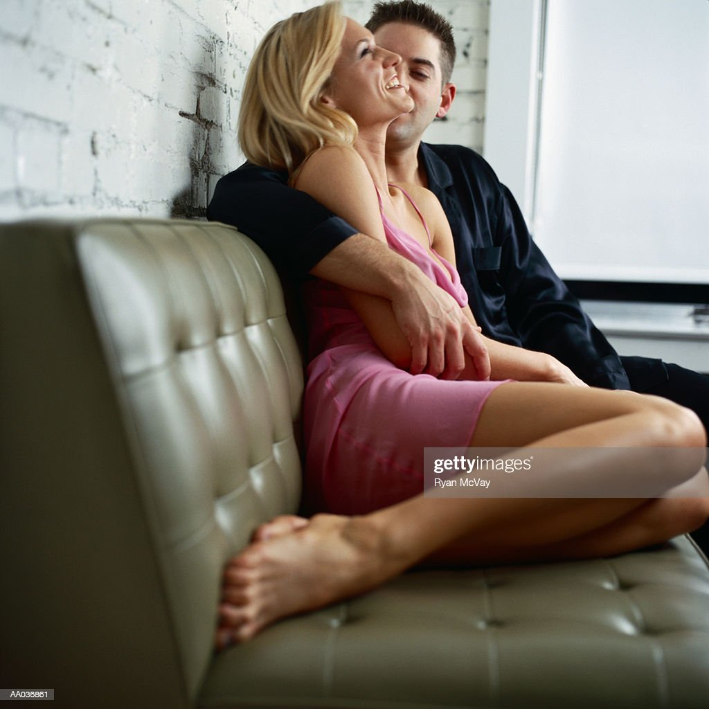 Young couple sitting on sofa, man's arm around woman, side view : Stock Photo