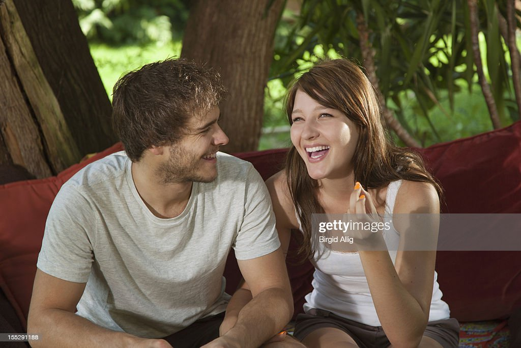 Young couple sitting on sofa outside,having fun : Stock Photo