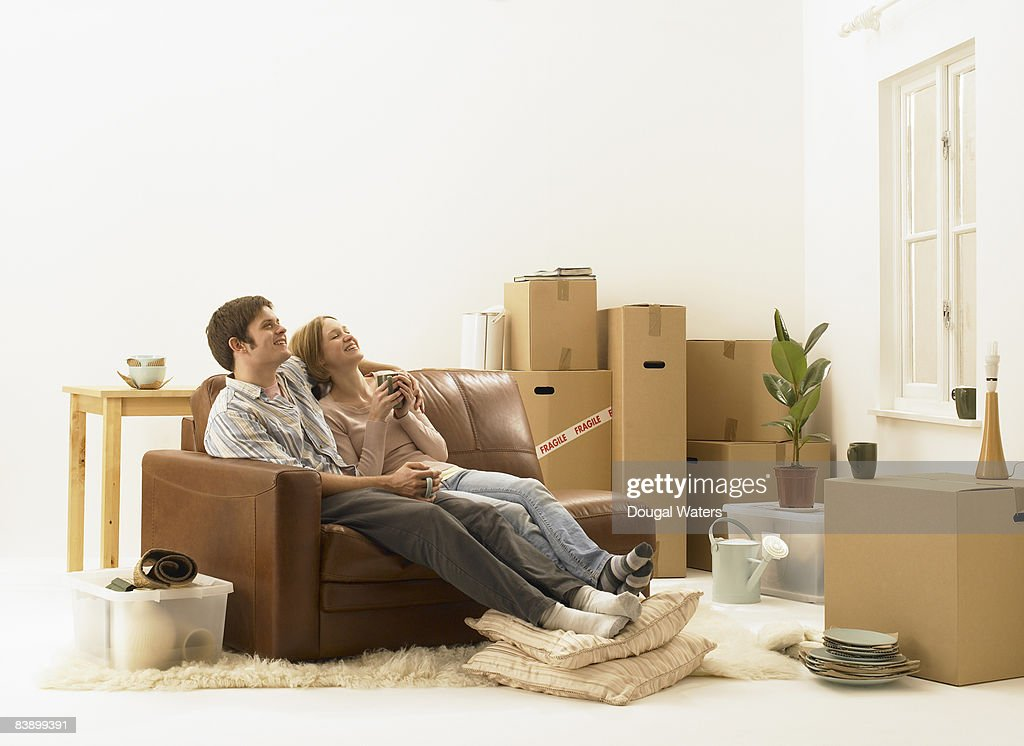 Young couple sitting on sofa, smiling. : Stock Photo