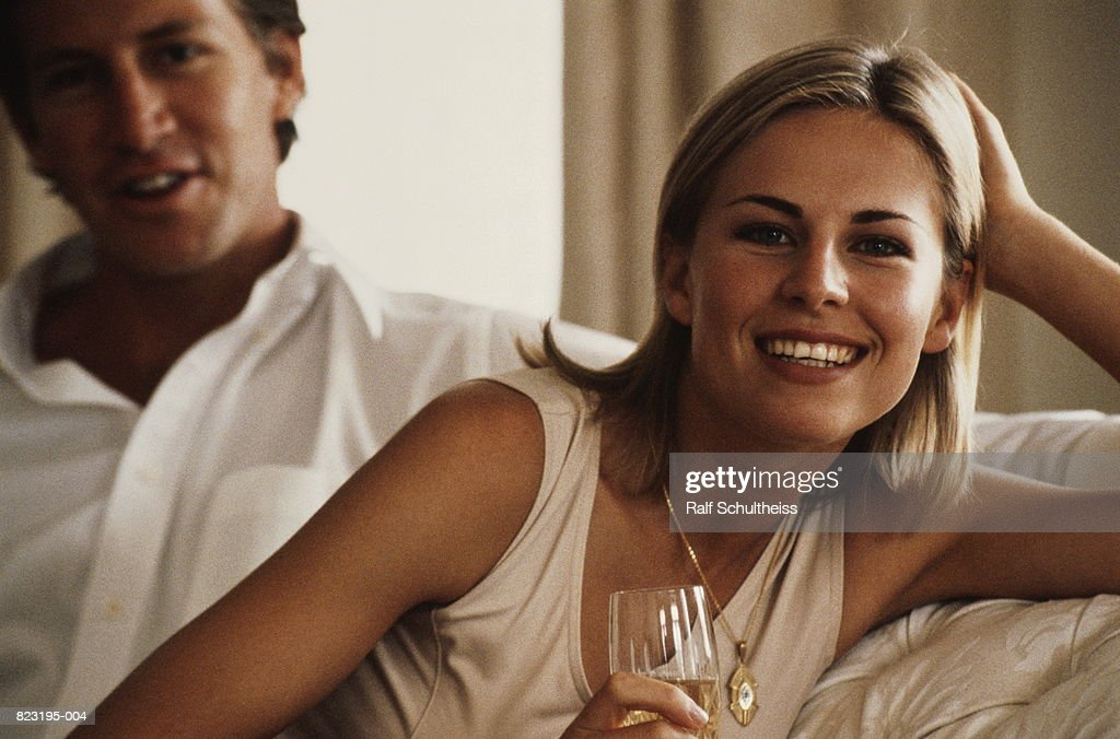 Young couple sitting on sofa, smiling, portrait (focus on woman) : Stock Photo