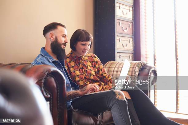 Young couple sitting on sofa using laptop