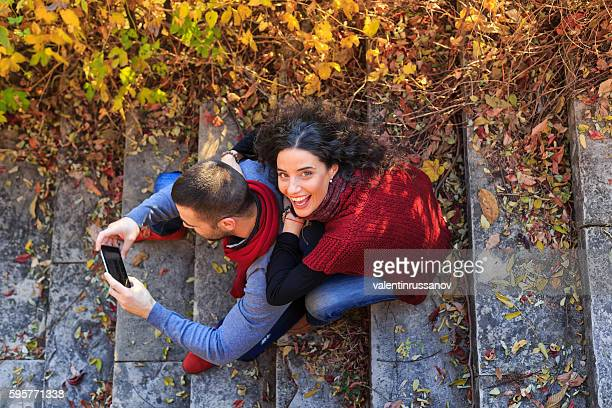 Young couple sitting on stairs and using smart phone