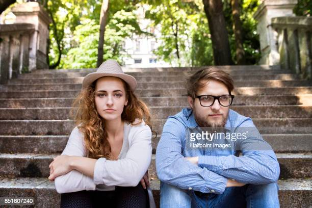 Young couple sitting on stairs in town.