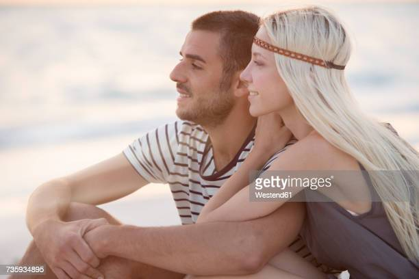 Young couple sitting on the beach, embracing