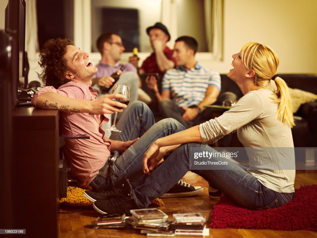 young couple sitting on the floor and watching TV : Stock Photo