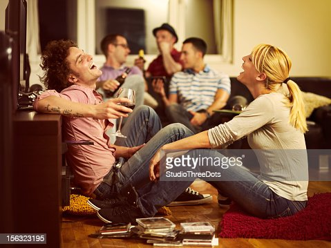 young couple sitting on the floor and watching TV