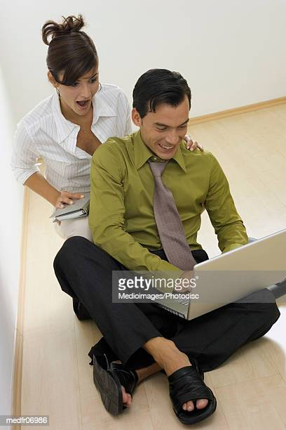 A young couple sitting on the floor operating a laptop