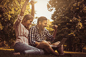Young couple sitting  on the grass. Happy couple using laptop.