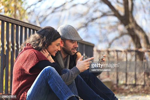 Young couple sitting on the ground and using smart phone