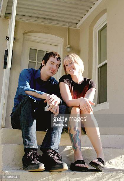 Young Couple Sitting on the Steps of Thier Frist Home