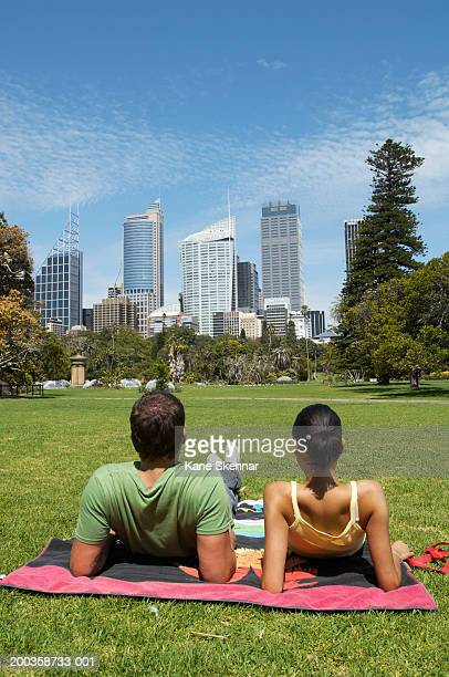 Young couple sitting on towel in park, rear view
