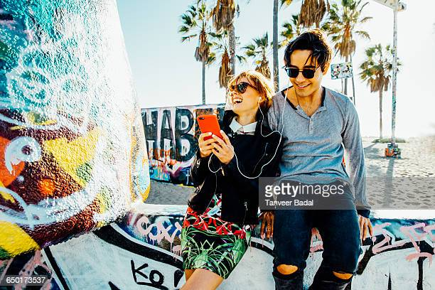 Young couple sitting on wall, sharing earphones, laughing
