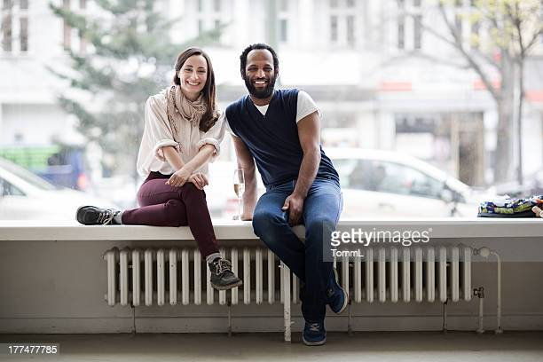 Young Couple Sitting On Window Sill in Gallery