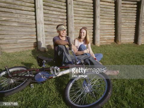 Young couple sitting together on grass talking : Stock Photo