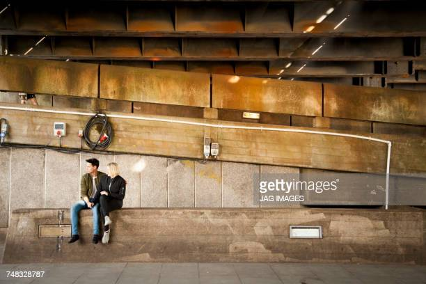 Young couple, sitting underneath bridge, relaxing