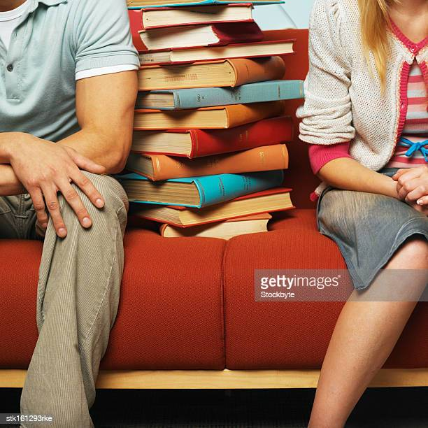 Young couple sitting with a pile of books on red sofa