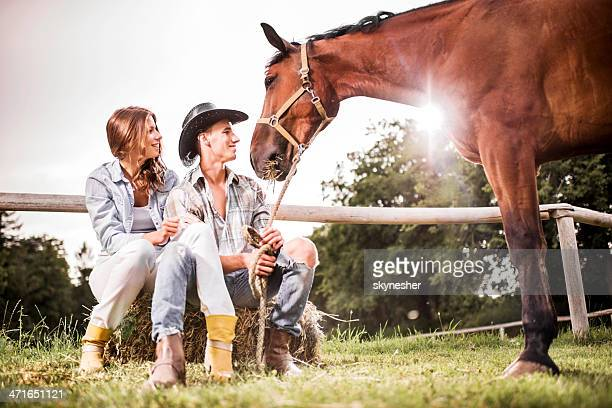 Young couple sitting with horse.