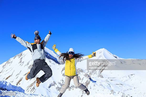 Young couple skiers having fun and jumping in the air