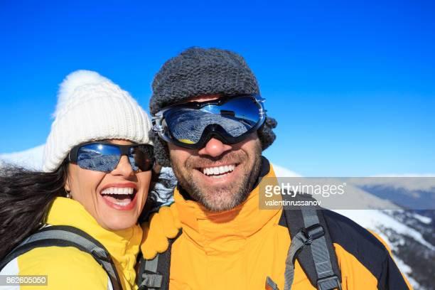 Jeune couple de skieurs s'amuser sur la montagne de neige haut de la page