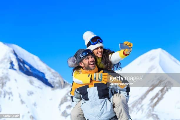 Junges Paar Skifahrer nehmen Selfie auf dem oberen Schneeberg