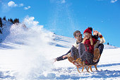 Young Couple Sledding And Enjoying On Sunny Winter Day.
