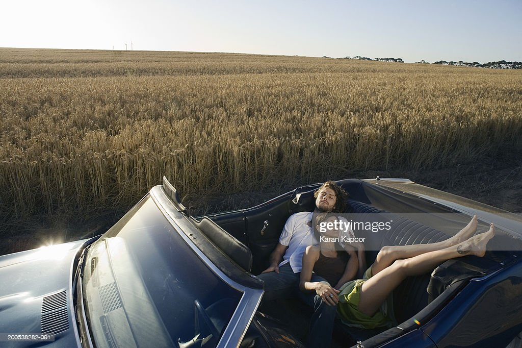Young couple sleeping in convertable car in wheat field : Stock Photo