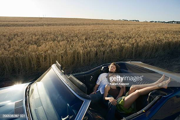Young couple sleeping in convertable car in wheat field