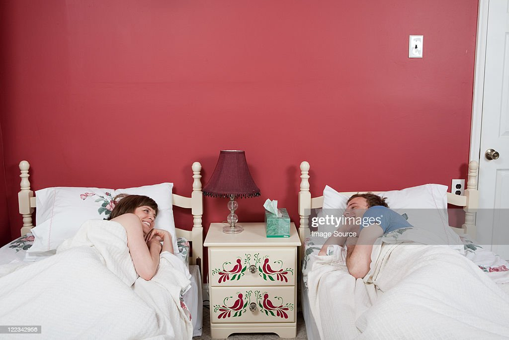 Young couple smiling at each other in single beds
