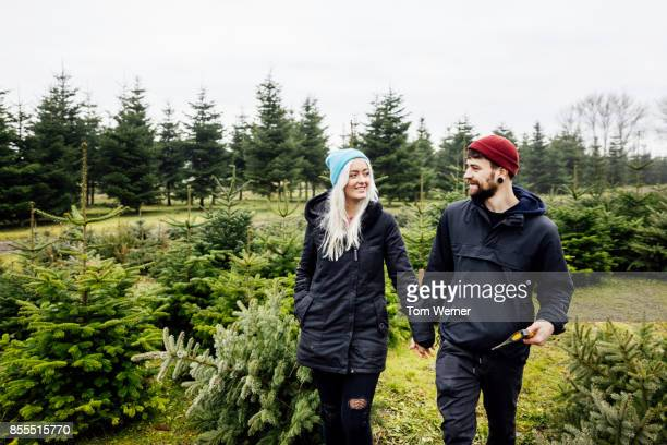 Young Couple Smiling At Eachother While Walking In Pine Woods