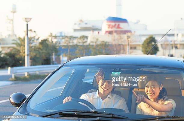 Young couple smiling in car, looking away