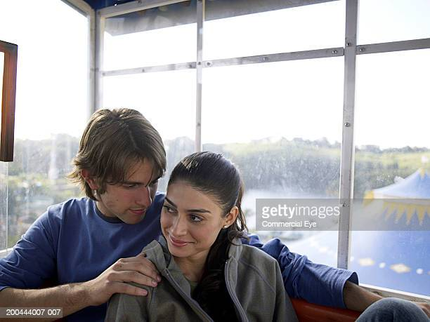 Young couple snuggling in Ferris wheel gondola, woman smiling