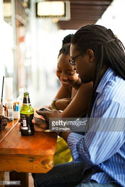 Young couple socialising and looking at a mobile phone. Cape Town, Western Cape Province, South Africa