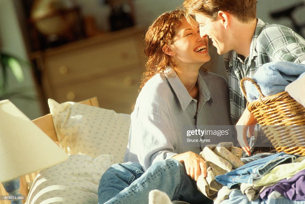 Young couple sorting laundry, laughing : Stock Photo