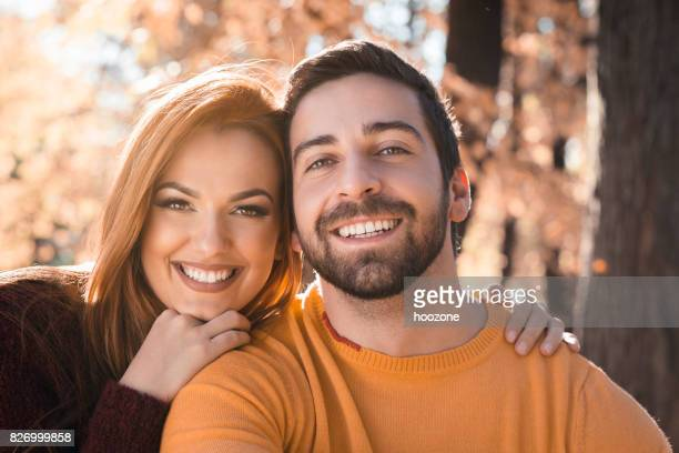 Young couple spending romantic time together in the public park, looking at camera.