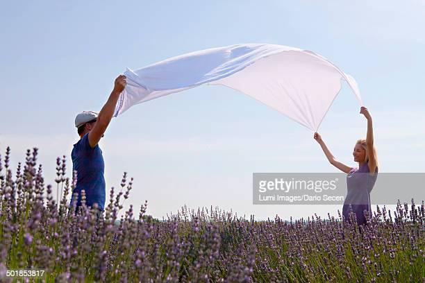 Young Couple Spreading Blanket In Lavender Field, Croatia, Dalmatia, Europe