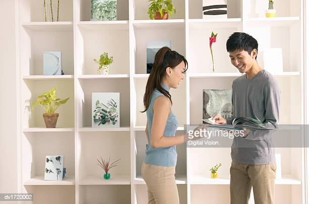 Young Couple Stand by a Shelving Unit in Their Home, Reading a Magazine