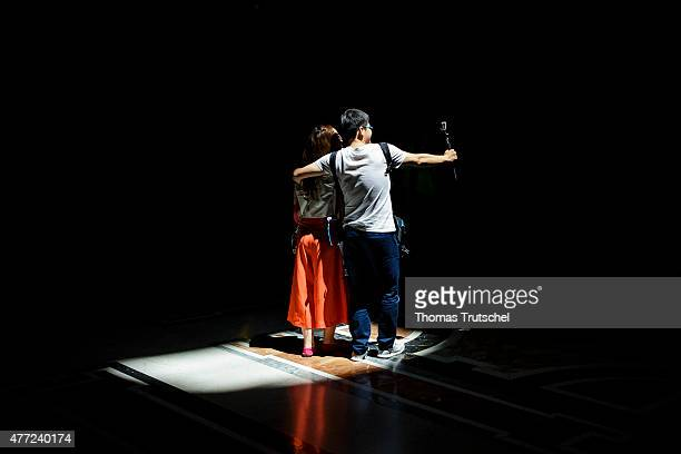 A young couple stand in a beam of light and take a selfie using a selfie stick on June 11 in Rome Italy