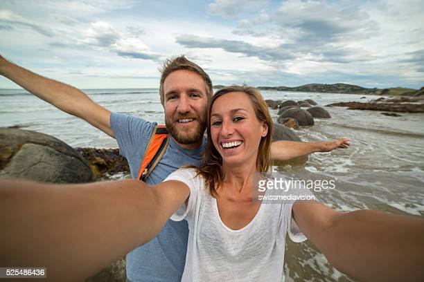 Young couple stand near Moeraki boulders and take selfie portrait