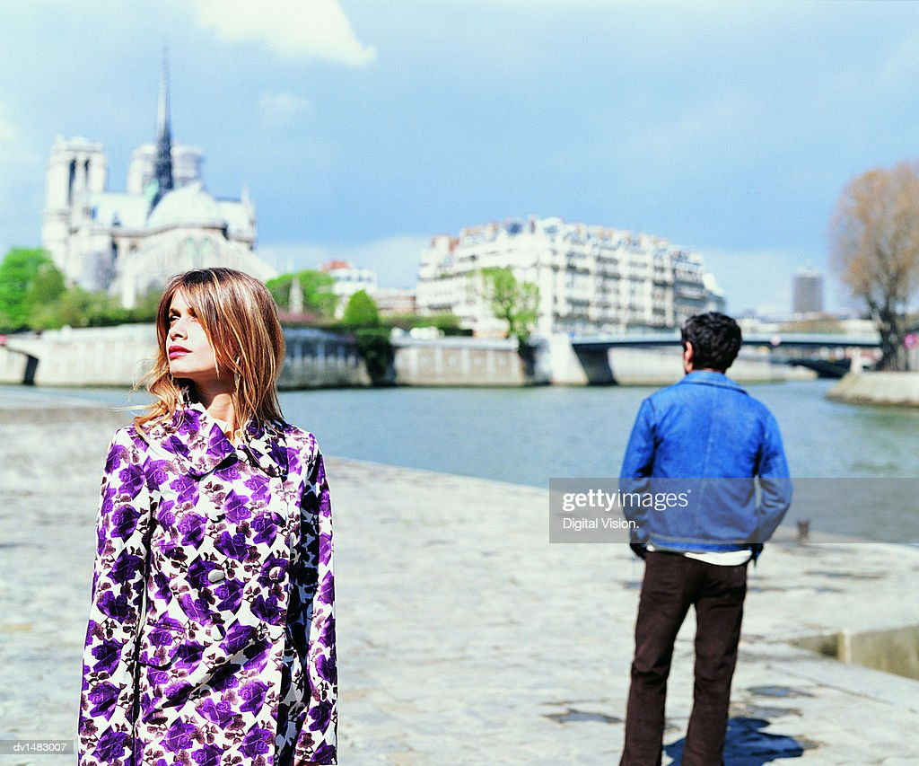 Young Couple Stand on the Left Bank of the River Seine with Notre Dame in the Background : Stock Photo