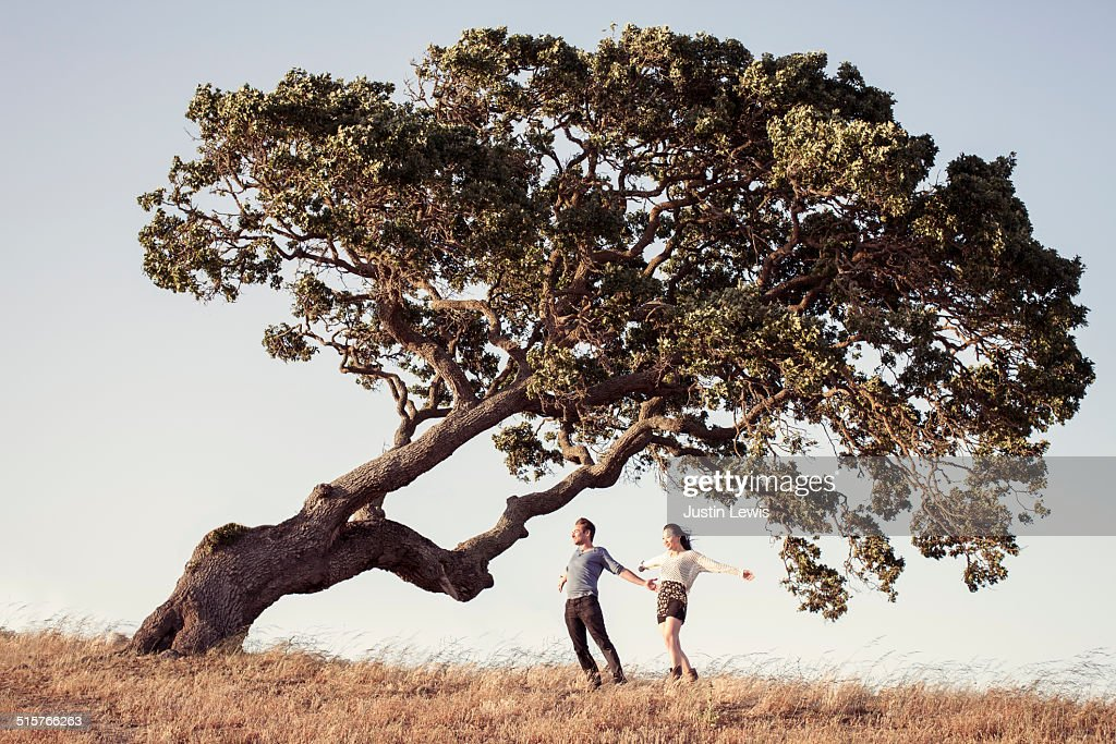 Young couple stand under ancient oak tree, windy