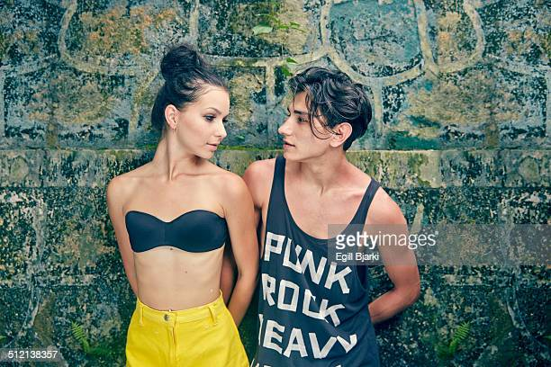 Young couple standing against wall, looking at each other