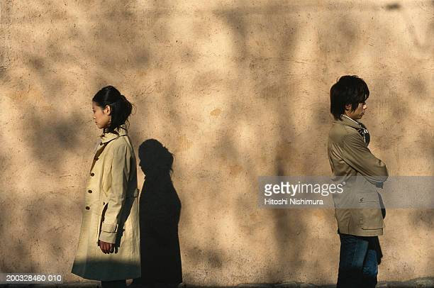 Young couple standing away outdoors, back to back