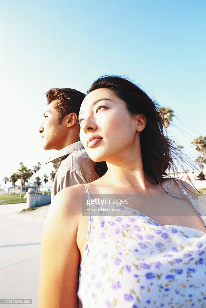 Young couple standing back to back, low angle view : Stock Photo