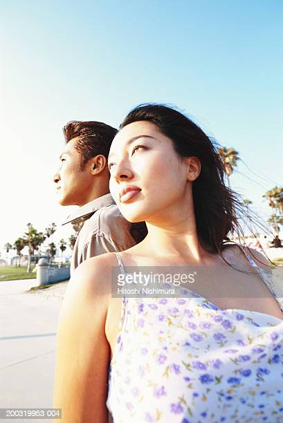 Young couple standing back to back, low angle view