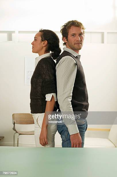 'Young couple standing back to back, side view'