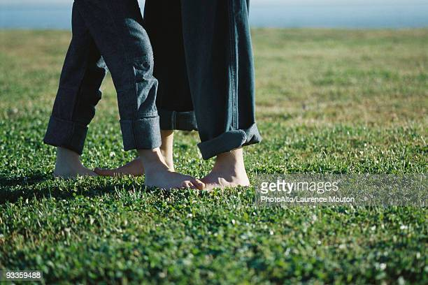 Young couple standing barefoot in field, low section