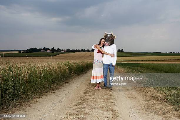 Young couple standing by field, man wearing bull mask