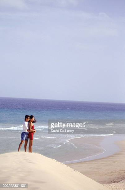 Young couple standing by ocean, side view